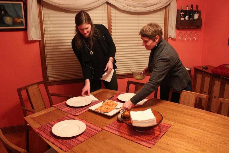 Erin Umhoefer (left) and her mother, Libbey Brennan, set the table for their weekly dinner date. The two women live together in an effort to save money.