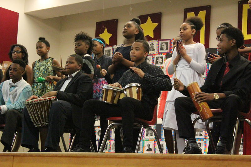 A few students team up to perform tribal African drum rhythms.