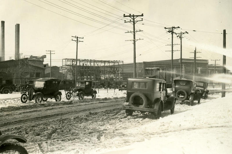 Several early model cars line a Milwaukee snow covered street in front of the A. O. Smith plant.
