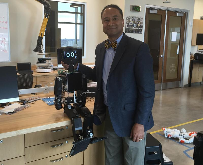 Marquette professor Andrew B. Williams poses with one of the creations in his robotics lab.