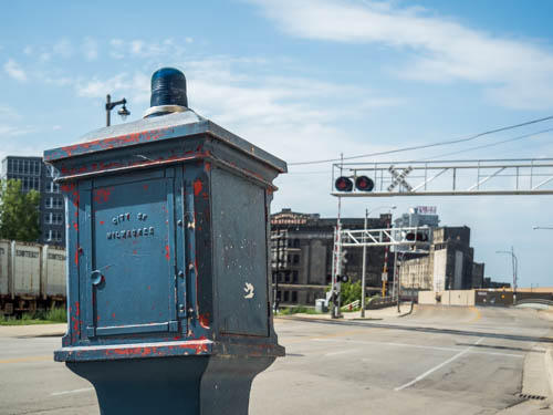 A blue police call box seated near the train tracks on Plankinton Ave. in downtown Milwaukee.