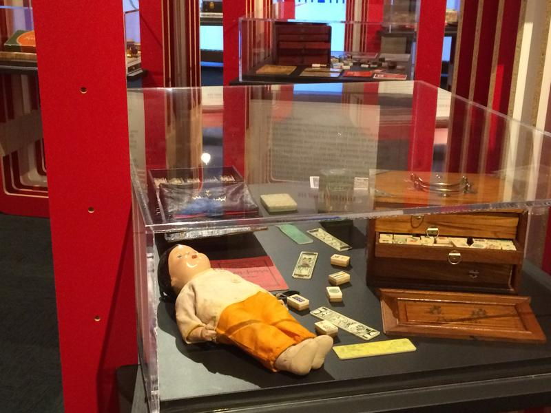 """Several display cases, filled with artifacts from the """"Project Mah Jongg"""" exhibit."""