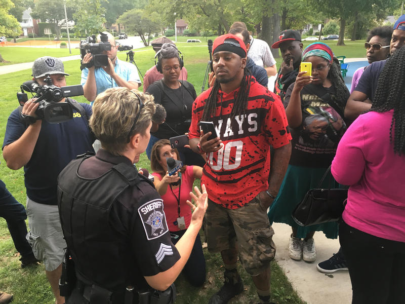 Vaun Mayes-Bey (center) discusses the Sherman Park curfew with a Sheriff's officer over Labor Day weekend -- three weeks a 6pm curfew went into effect.