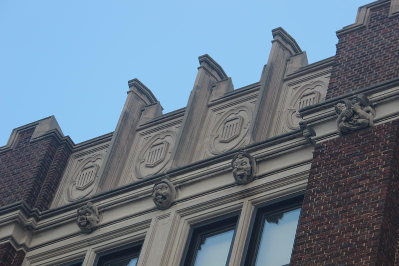 Stone faces line the top of Bay View High School