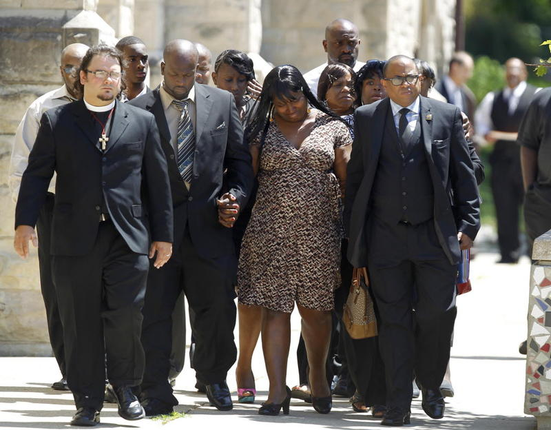 Patricia Larry, mother of Darius Simmons, center is joined by Bishop Tavis Grant, right, (with glasses) national field director for the Rainbow PUSH Coalition as the family is escorted into church for the funeral of Darius Simmons.