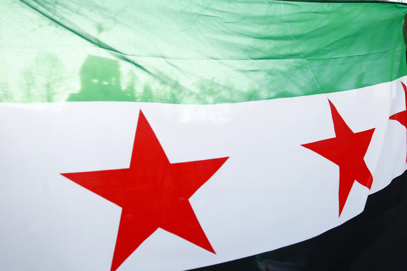 Protesters hold a Syrian flag during a demonstration to demand an end to Russian aerial bombing of the Syrian city of Aleppo in front of the Russian Embassy on December 7, 2016 in Berlin, Germany