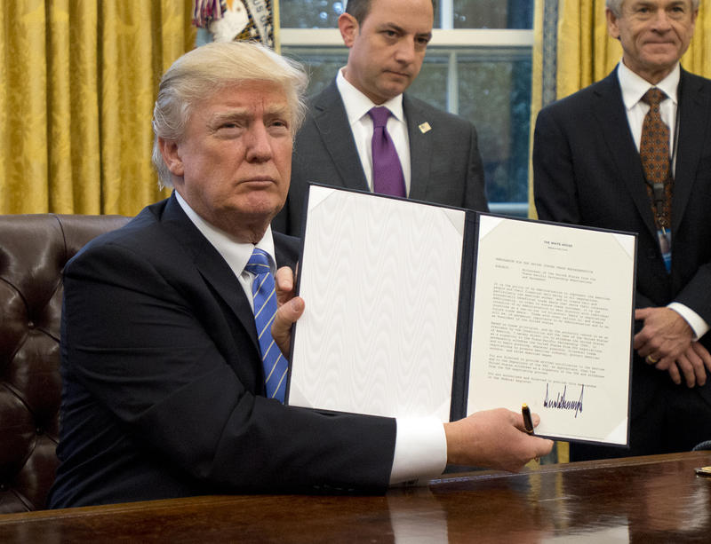 U.S. President Donald Trump shows the Executive Order withdrawing the US from the Trans-Pacific Partnership (TPP) after signing it in the Oval Office of the White House in Washington, DC on Monday, January 23, 2017.
