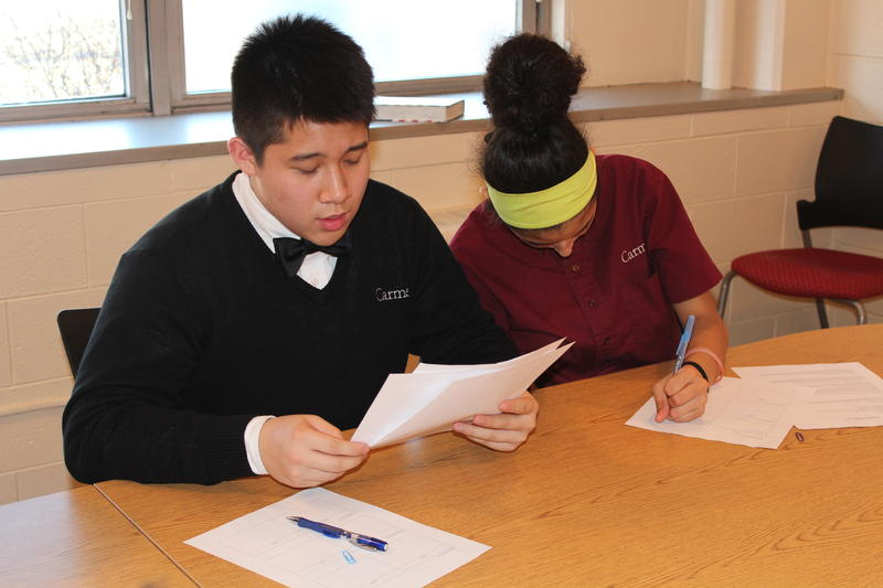 Carmen High school freshman read through materials on the three candidates for Wisconsin state Superintendent.