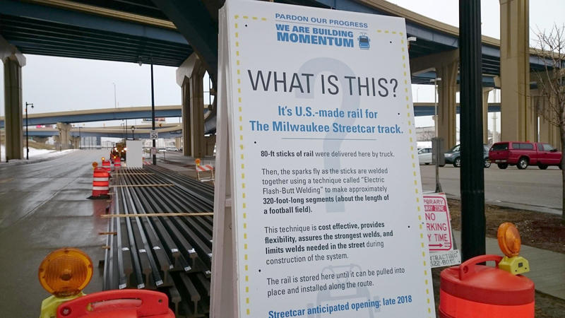 What is this? A sign explains that passersby are seeing the first segments of track for the Milwaukee streetcar.