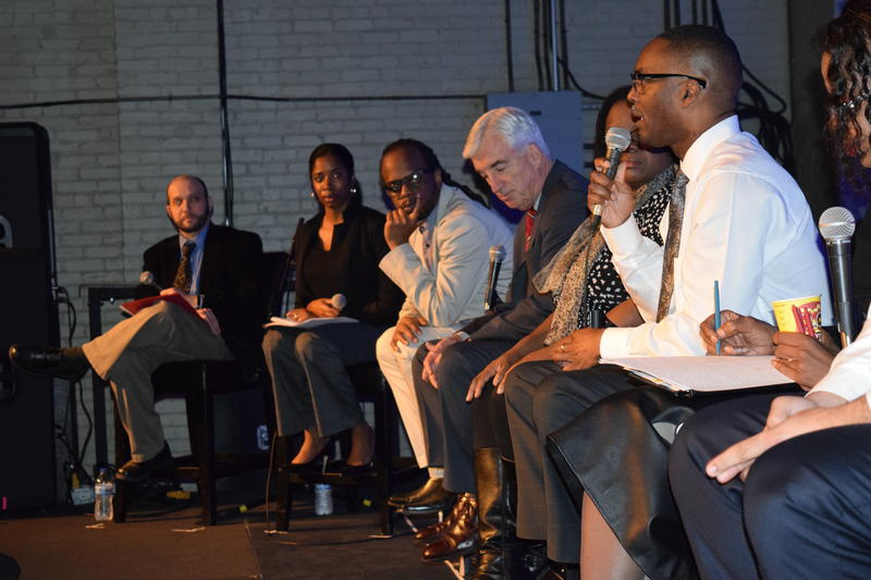 Reggie Jackson speaking as other panelists listen at the live forum.