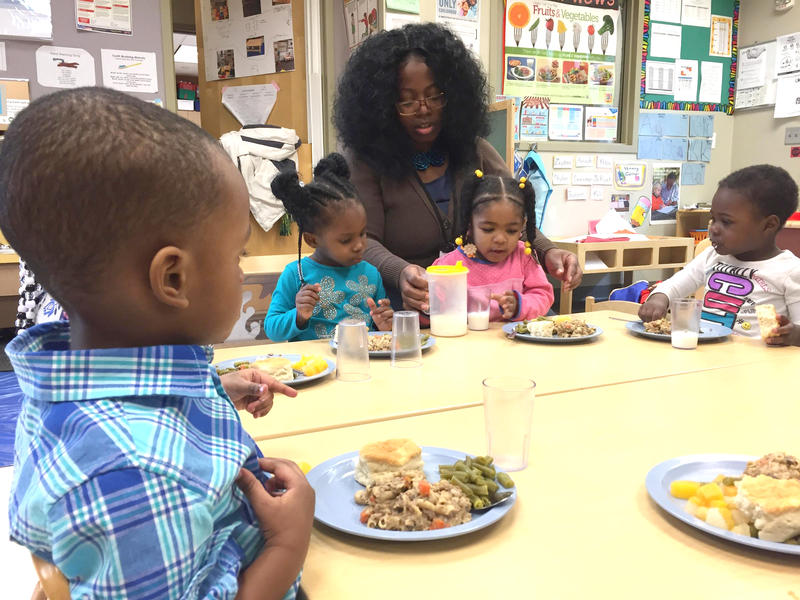 Teachers help two- and three-year-old students prepare to eat lunch in a Milwaukee Educare classroom.