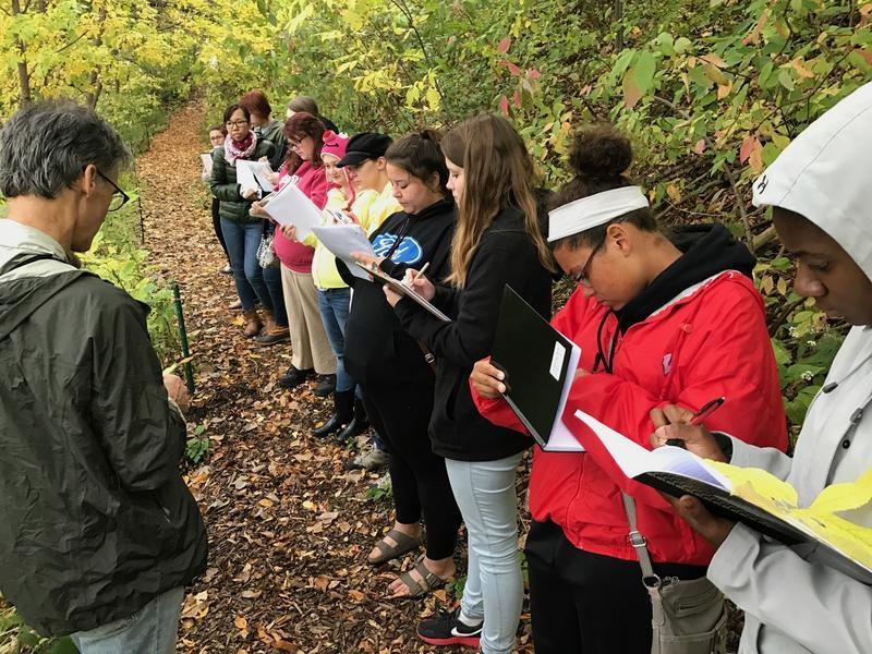 Alverno students survey Menomonee River natural area within Three Bridges Park.