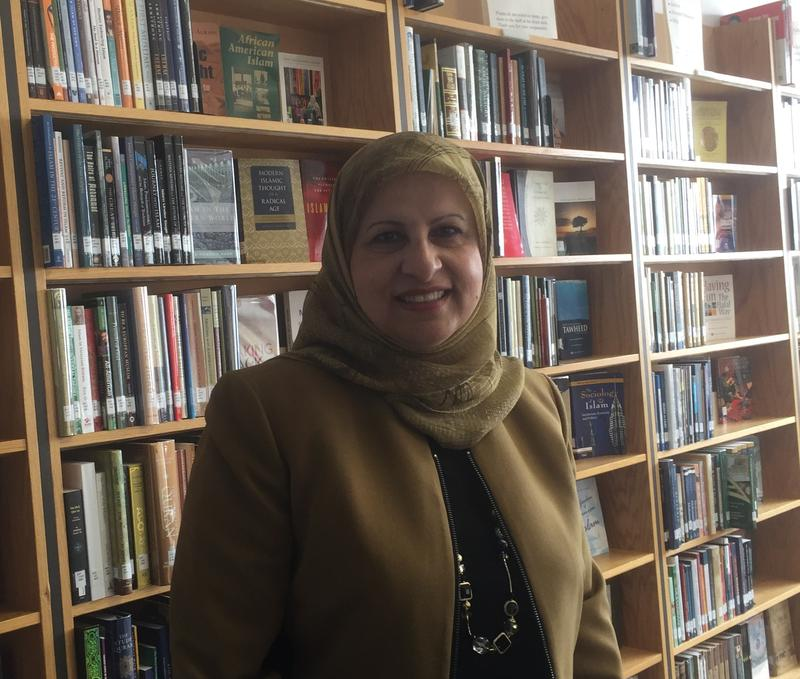Milwaukee Muslim Women's Coalition President Janan Najeeb stands next to just a few of the thousands of books and DVDs in the Islamic Resource Center's library