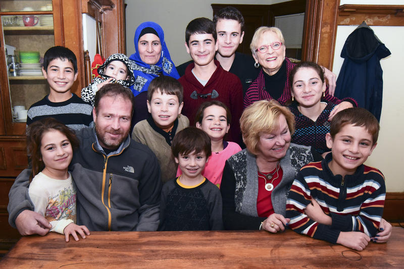 The Hamdoun family, posing with some Holy Angels volunteers. Hussein Hamdoun  stand in the farthest back row, center, next to volunteer Marian Yoder Catania.