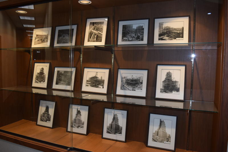 Wall of pictures showing construction progress inside building.