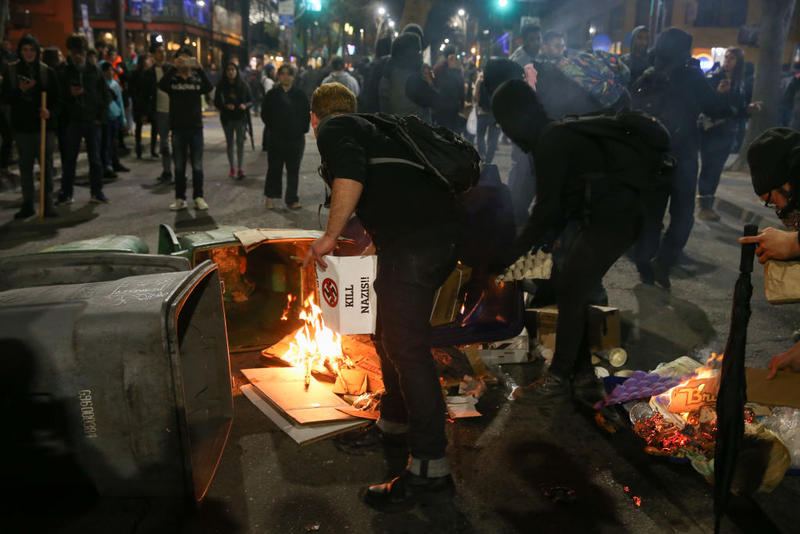 People protesting controversial Breitbart writer Milo Yiannopoulos burn trash and cardboard in the street on February 1, 2017 in Berkeley, California.
