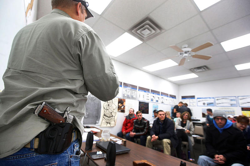 With a gun on his hip, gun instructor Mike Stilwell, demonstrates an semi automatic hand gun as as he teaches a packed class to obtain the Utah concealed gun carry permit, at Range Master of Utah.