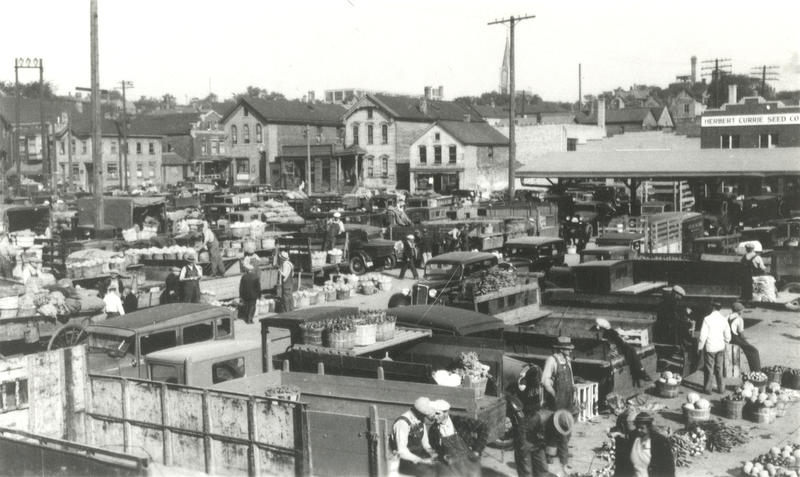 Historic photo of a large number of trucks parked in Milwaukee's Central Market full of baskets of produce to sell.