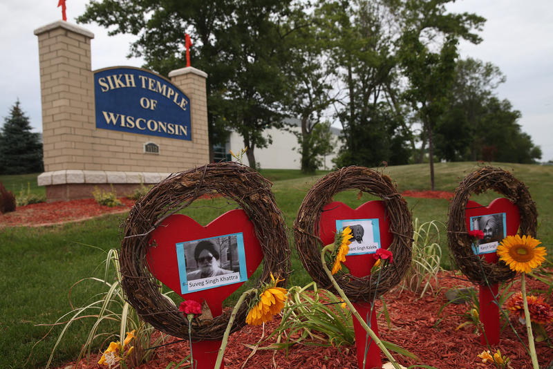 Pictures of the victims of the shooting at the Sikh Temple of Wisconsin sit in front of the temple during a service held to mark the one-year anniversary of the shooting rampage that killed six members of the temple August 5, 2013 in Oak Creek, Wisconsin.