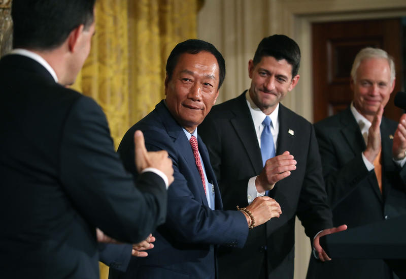 Terry Gou (2nd L), chairman of Apple supplier Foxconn, shakes hands with Wisconsin Gov. Scott Walker (R) as House Speaker Paul Ryan looks on at news conference held by U.S. President Donald Trump in the East Room of the White House.