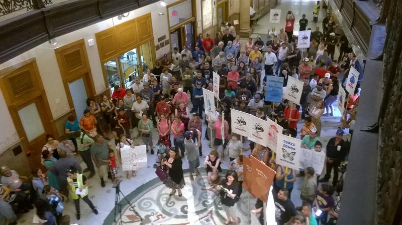 Immigrants in immigration activists protested in the Milwaukee City Hall rotunda before a Fire and Police Commission meeting where members would vote on changes to police policy