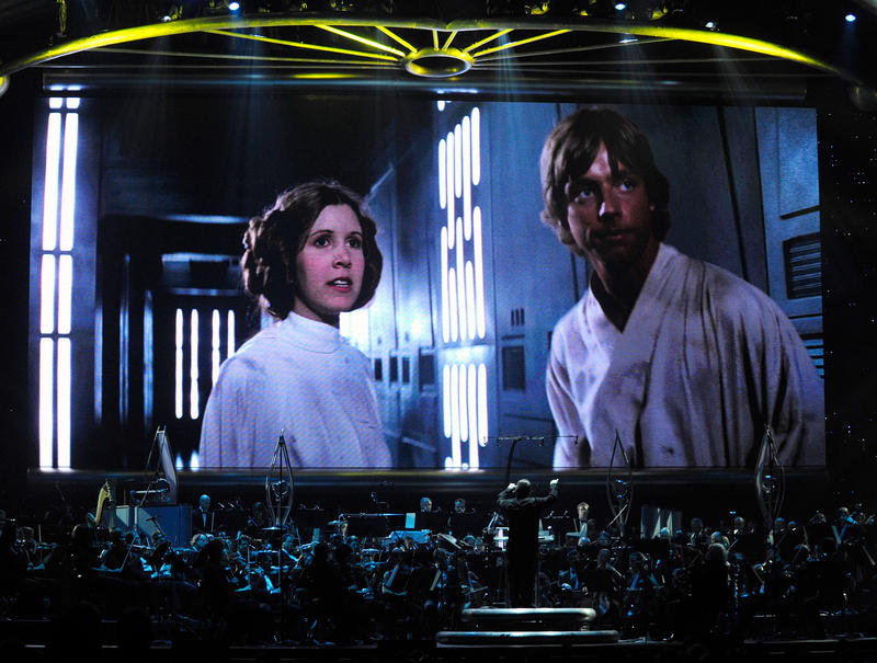 Actress Carrie Fisher's Princess Leia Organa character and actor Mark Hamill's Luke Skywalker character from 'Star Wars Episode IV: A New Hope' are shown on screen while musicians perform during 'Star Wars: In Concert' at the Orleans Arena May 29, 2010.