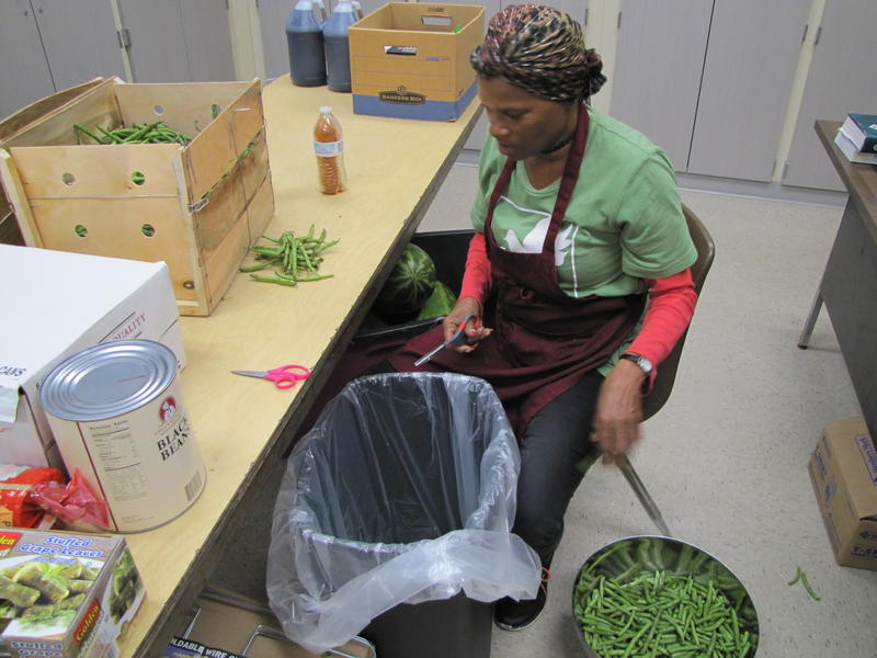 As breakfast is cooked, Anita Baker prepares fresh beans for lunch.