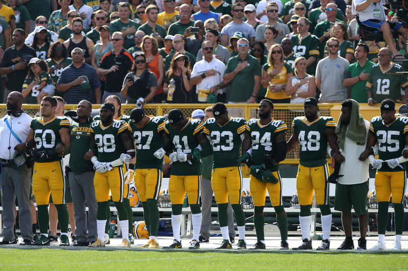 Members of the Green Bay Packers stand with arms locked as a sign of unity during the national anthem prior to their game against the Cincinnati Bengals at Lambeau Field on September 24, 2017 in Green Bay, Wisconsin.
