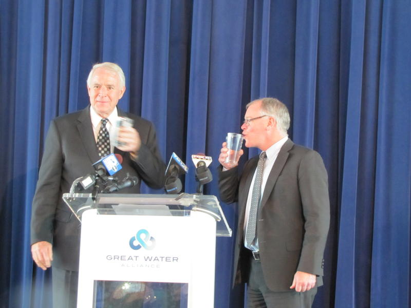 Mayors Tom Barrett and Shawn Reilly raise a glass to their water agreement Monday afternoon.