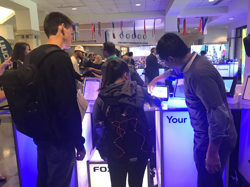 Product manager Jim C.Y. Chu (far right), shows Marquette students a few of the features on one of their LCD monitors.