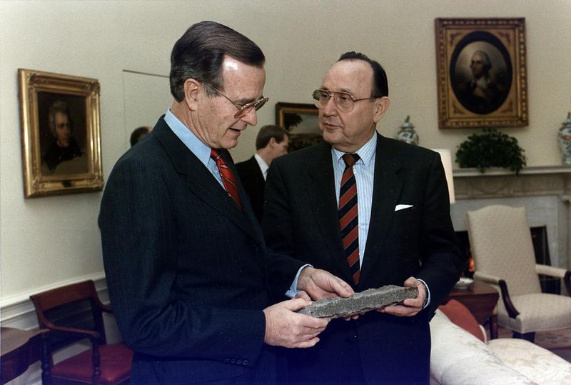 U.S. President George Bush is presented with a piece of the Berlin Wall by West German Foreign Minister Hans-Dietrich Genscher in the Oval Office, 21 November 1989.