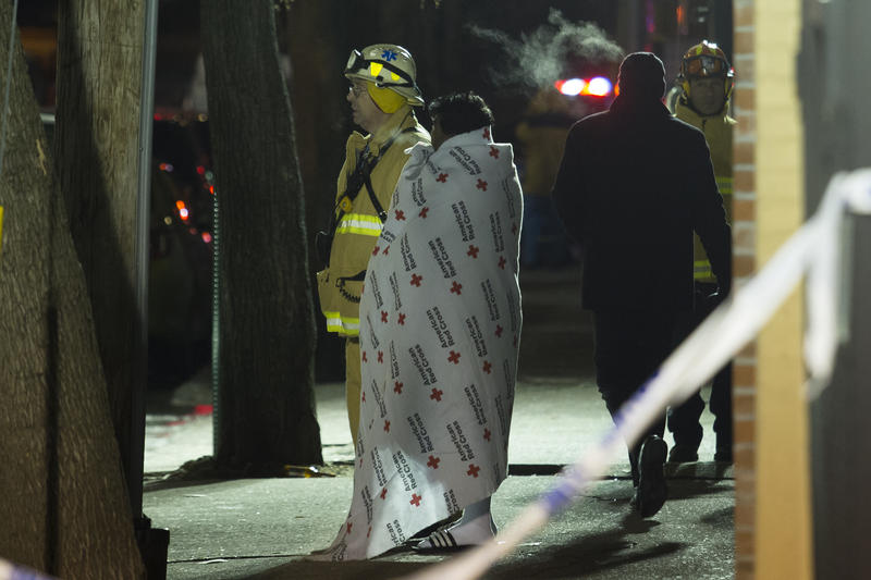 A woman covered with a Red Cross blanket talks to a fire fighter during a major house fire on December 28, 2017 in the Bronx borough of New York City.