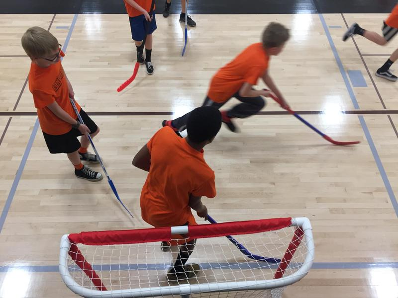 Seventh graders at Longfellow Middle School play a competitive game of floor hockey in physical education class.