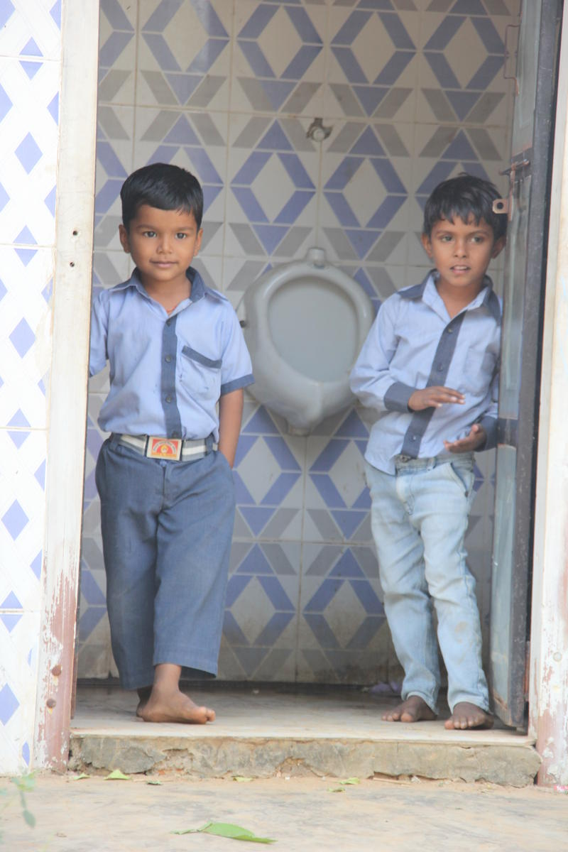 Friends peer out from a bathroom doorway at a rural school in Agra.