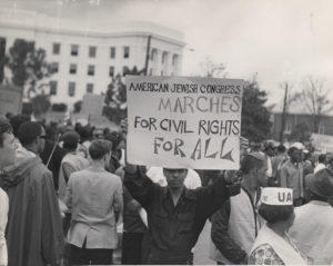 Black demonstrator holding American Jewish Congress sign in front of State Capitol, Montgomery, Ala., at climax of Selma-to-Montgomery march, March, 1965