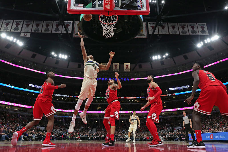 Giannis Antetokounmpo #34 of the Milwaukee Bucks rebounds over David Nwaba #11 (L) and Denzel Valentine #45 of the Chicago Bulls at the United Center on January 28, 2018 in Chicago, Illinois. The Bucks defeated the Bulls 110-96.