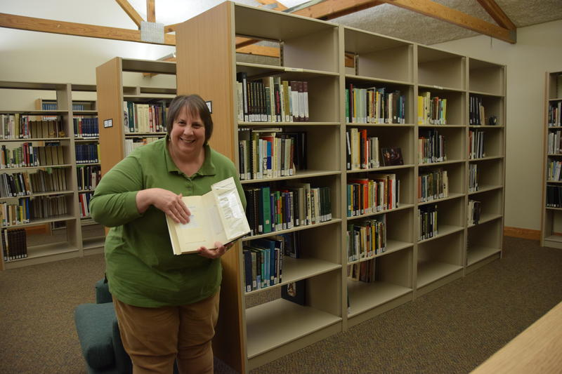 While the library is up-to-date with technology, librarian Mary Kazmierczak demonstrates that patrons still sign out books the old-fashioned way - with a card in the back.