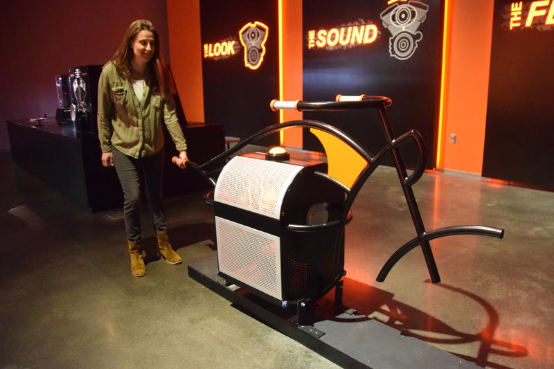 Kristen Jones with a display that allows visitors to experience the feel of a Harley Davidson motorcycle engine.