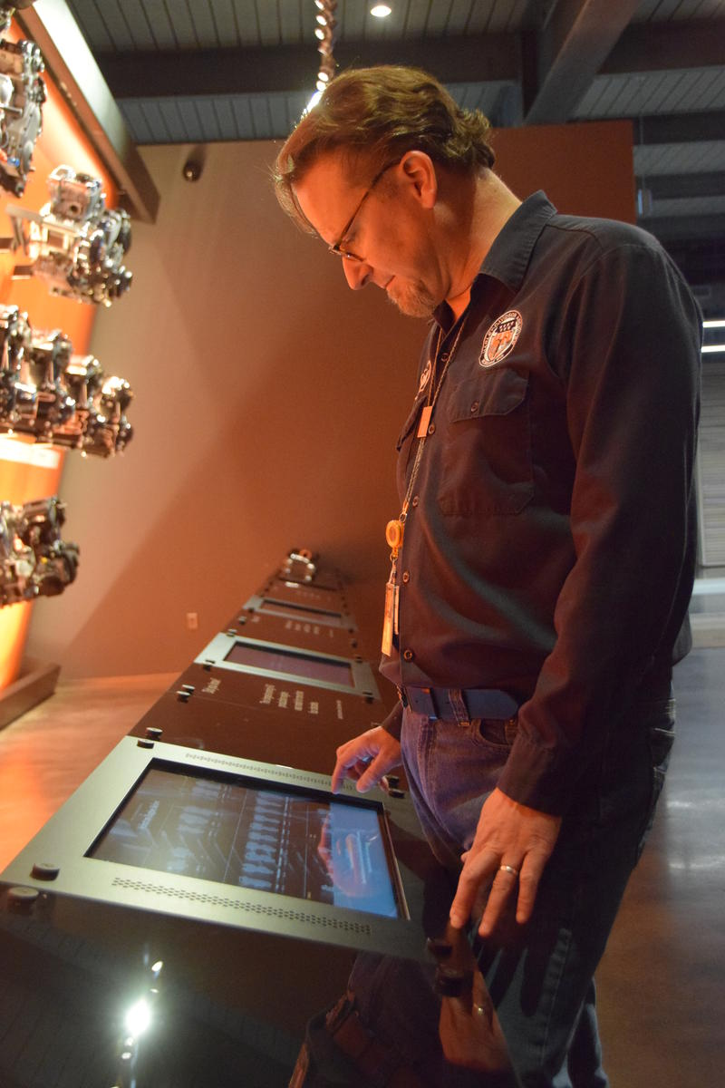 Bill Rodencal demonstrates the interactive display that allows visitors to hear a variety of Harley Davidson engines from more than a hundred years of history.