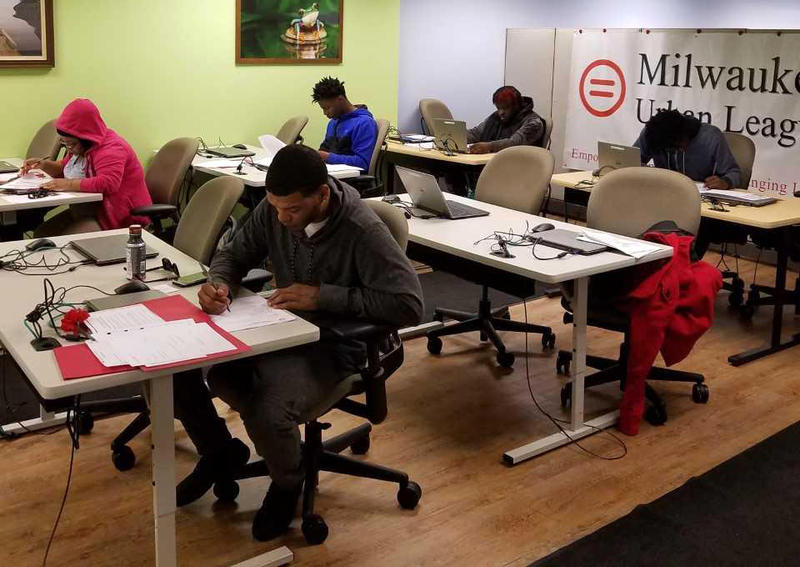 Job seekers fill out forms at a general job search workshop at the Milwaukee Urban League.