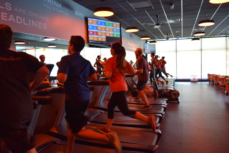Participants run while monitoring their heart rates on the screen nearby at Orangetheory Fitness in Shorewood, WI.