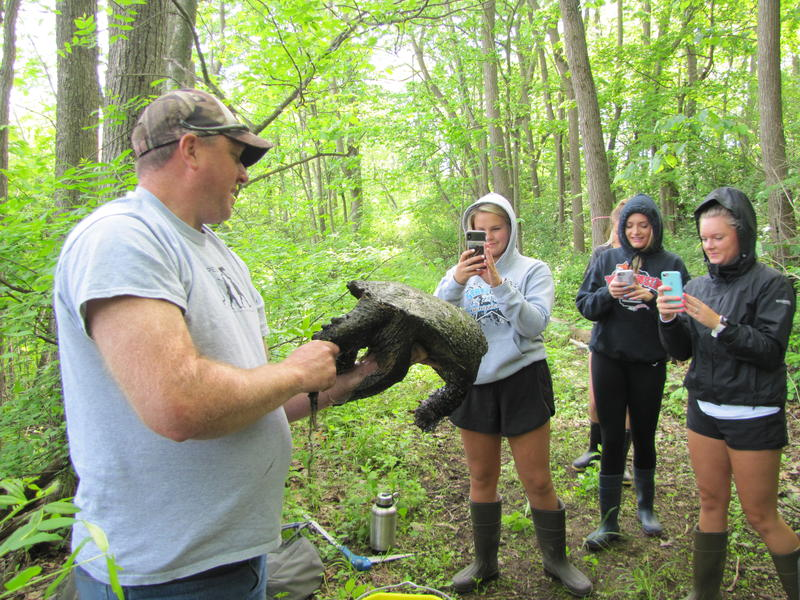 Franklin High School teacher Patrick Gain introduces his students to a large snapping turtle that makes the conservancy its home.