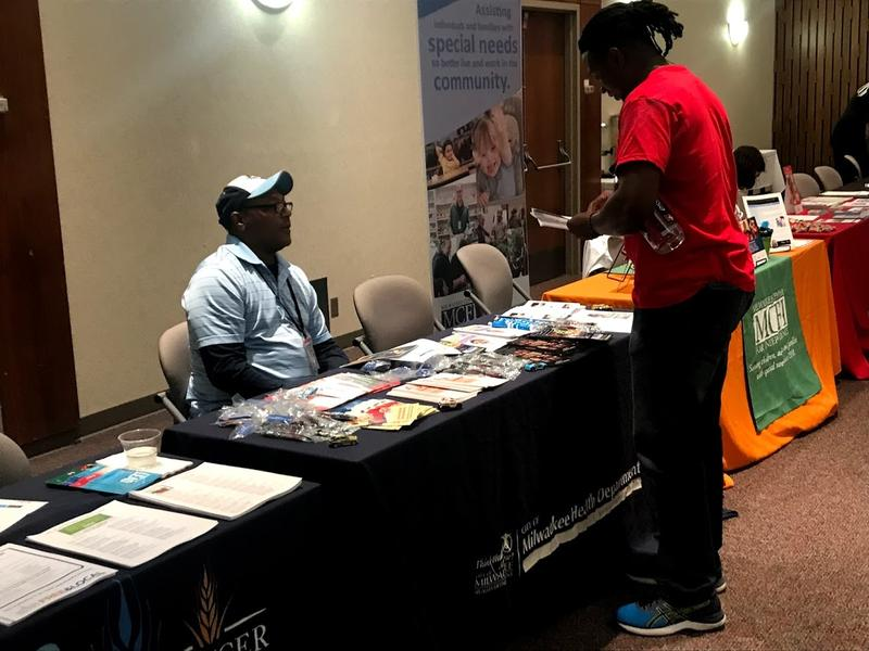 A guest gets information from the Milwaukee Health Department vendor at the health fair.