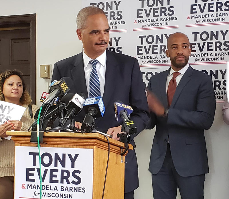 Eric Holder speaks at a press conference for Wisconsin candidate for governor Tony Evers as Evers' running mate Mandela Barnes looks on.