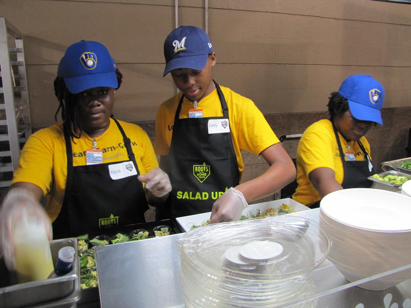 ROOTS For The Home Team members Kayla Thomas, Corey Stevenson & Lynett Wheeler prepare salads at Miller Park.