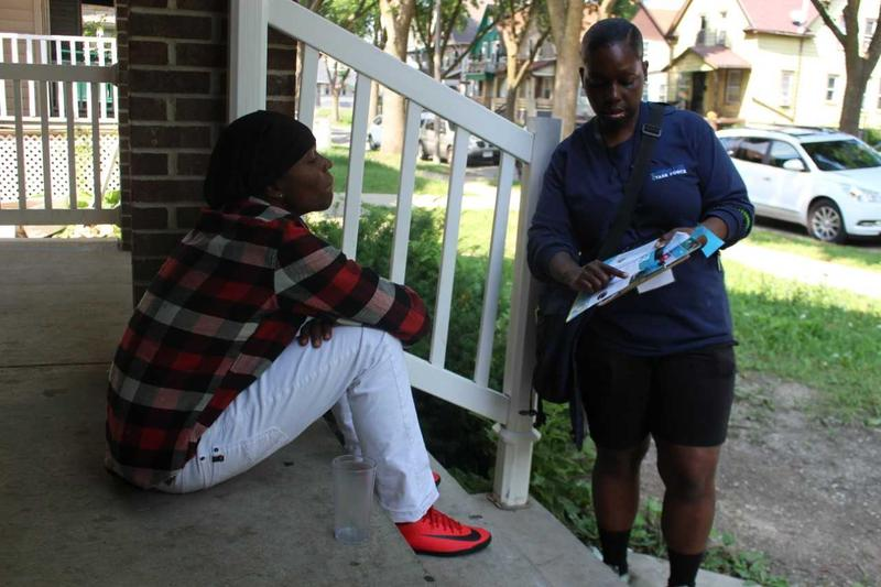 Canvasser Orean Harper shares lead information with an Amani neighorhood resident.