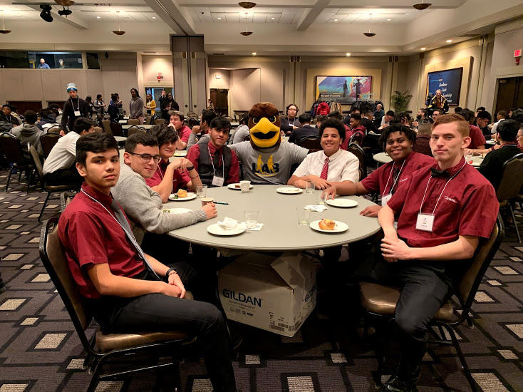 Teens with the Marquette University Golden Eagles mascot at the Leadership and Brotherhood Summit for Young Men of Color.
