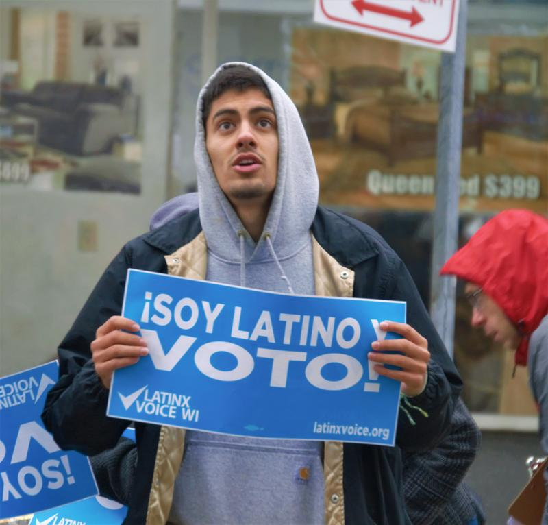 Abraham Alvarez held a sign proclaiming that he's Latino, and he votes. He was casting his ballot on Milwaukee's near south side.