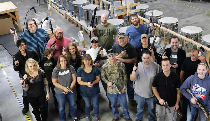 Wisconsin-based BenShot employees hold guns, which were company Christmas presents to those who accepted.