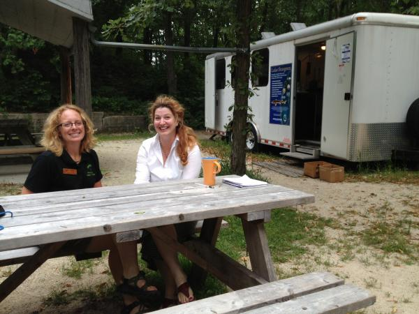 Executive director Jessica Jens (left) and development director Julia Courtright outside sturgeon rearing trailer.